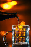 Dark beer is poured into a glass mug from a bottle Royalty Free Stock Photos