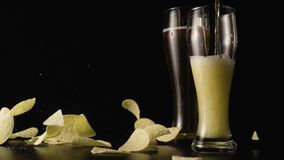 Dark beer is poured into a glass of potato chips falling in slow mo stock footage
