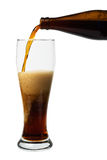 Dark beer pouring into a glass Stock Images