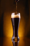 Dark beer pouring Stock Photography