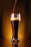 Dark beer pouring Stock Photos