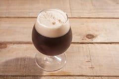 Dark beer on wood Stock Images
