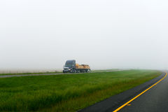 Dark big rig semi truck flat bed trailer lumber cargo foggy road Royalty Free Stock Photography