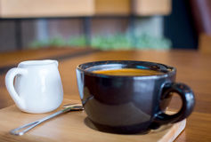 Dark black blue coffee cup with americano coffee, spoon and a milk jug on a wooden stand Royalty Free Stock Images