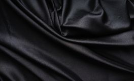 Dark black silky, satin  fabric, wave, draperies. Beautiful textile backdrop. Close-up. Top view Stock Images