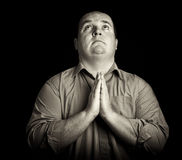 Dark black and white overweight male praying Royalty Free Stock Photography