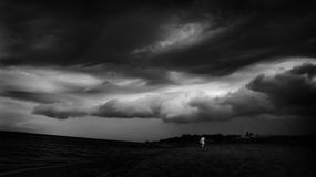 Dark black-and-white storm, sea, clouds. Dark black-and-white image of a storm, sea, clouds and persons silhouette Royalty Free Stock Photography