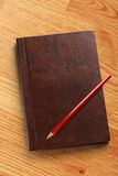 Dark blank notebook with red pencil Stock Images