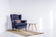 Dark blue armchair on brown carpet stock image