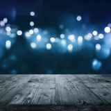 Dark blue background with light effects. Wintry dark blue background with white bokeh in front of a empty wooden stage for a presentation stock image