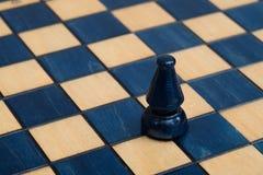 Dark blue bishop on wooden chessboard Royalty Free Stock Photos