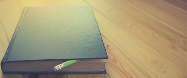 Dark blue book on brown wooden table. Dark blue book with pencil on brown wooden table for background, the blank space on the left for text Royalty Free Stock Images