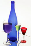 Dark blue bottle and three wine-glasses Royalty Free Stock Photography