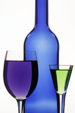 Dark blue bottle and two wine-glasses. Facing it Stock Images