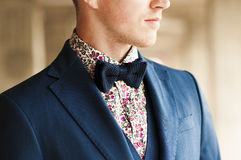 Dark blue bow tie with flowers shirt and suit on men's neck. Royalty Free Stock Image