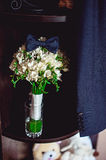 Dark blue bow tie on a luxury bridal bouquet of white flowers on a shelf Stock Images