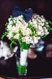 Dark blue bow tie on a luxury bridal bouquet of white flowers on a shelf Stock Photography
