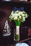 Dark blue bow tie on a luxury bridal bouquet of white flowers on a shelf Stock Photos