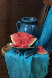 Dark blue ceramic jug and ripe water-melon on a copper dish Royalty Free Stock Images