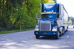 Dark blue classic monster big rig semi truck trailer chrome on i Stock Photo