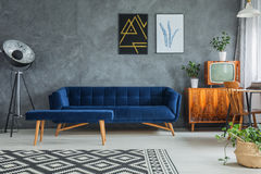 Dark comfy couch. Dark blue comfy couch with matching footrest and wooden cupboard with retro TV Royalty Free Stock Image