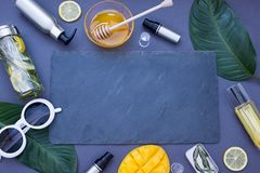 Dark blue cosmetic frame . Top view. Dark blue cosmetic frame with honey, mango, glasses and lemon. Top view Stock Image