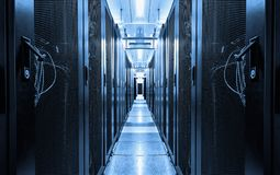 Dark blue data centre interior with rows of hardware equipment. Specialized building for hosting server and network equipment and
