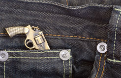 Dark blue denim jeans with a gun Royalty Free Stock Image