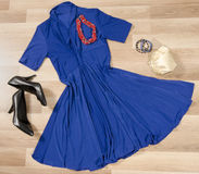 Dark blue dress and accessories arranged on the floor. Woman dress with accessories, purse, high heel shoes and necklace Royalty Free Stock Image