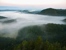 Dark blue fog in deep valley after rainy night. Rocky hill bellow view point. The fog is moving between hills and peaks of trees. Stock Photo