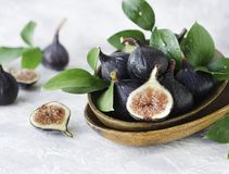 Dark blue Fresh figs in a wooden bowl on a white marble table, selective focus Stock Photos