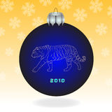 Dark blue fur-tree ball. With a tiger on an orange background with snowflakes Royalty Free Stock Photography