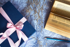 Dark blue gift box with  ribbon decoration with book and flower Stock Image