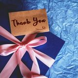 Dark blue gift box with  ribbon decoration and Thank You card. The Dark blue gift box with  ribbon decoration and Thank You card  on polka blue paper  , top view Stock Images