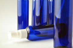 Dark blue glass bottles for cosmetic lotions, serums, oils. Glass bottles for cosmetic lotions, serums, essential oils and liquids with copy space Stock Image