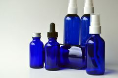Dark blue glass bottles for cosmetic lotions, serums, oils. Glass bottles for cosmetic lotions, serums, essential oils and liquids with copy space Royalty Free Stock Photos
