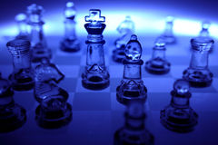 Dark blue glass chessboard. Dark blue tones dominated this glass chessboard and its pieces Royalty Free Stock Photo