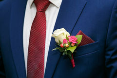 Dark blue groom`s suit and boutonniere of white and red roses Stock Photos