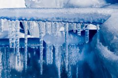 Dark Blue Icicles growing on Ice Stock Photo