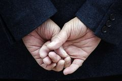 Crossed fingers. Dark blue jacket and two hands with crossed fingers Royalty Free Stock Photos