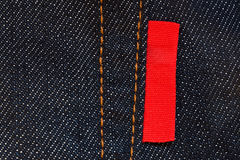 Dark blue jeans background with empty red label Stock Photos