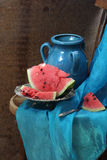 Dark blue jug and ripe water-melon on a copper dish Royalty Free Stock Images