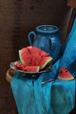 Dark blue jug and ripe water-melon on a copper dish. Water-melon piece on a copper dish and a dark blue jug on a wooden table Stock Photos