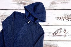 Dark blue knit cardigan. Brand hooded jacket for little boys on old wooden background. Childrens outfit on sale Stock Photos