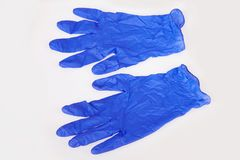 Dark blue latex medical gloves on white background. stock image