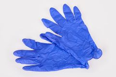 Dark blue latex medical gloves on white background. stock photography