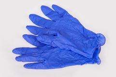 Dark blue latex medical gloves on white background. stock photo