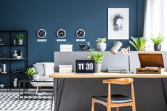 Dark blue interior with workspace. Dark blue living room interior with black industrial racks and stylish workspace by a gray half wall Stock Photography