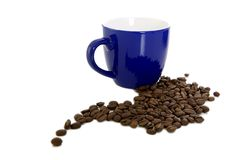 Dark blue mug and scattered coffee Royalty Free Stock Images