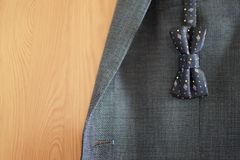 Dark blue patterned bow tie on grey suit jacket background. Dark blue patterned bow tie and grey suit jacket on brown wood background. Happy Fathers day or Stock Photography